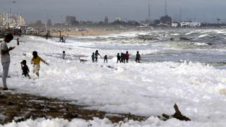 Children play on Marina beach in Chennai, India, which is blanketed in sea foam, Dec.1, 2019.