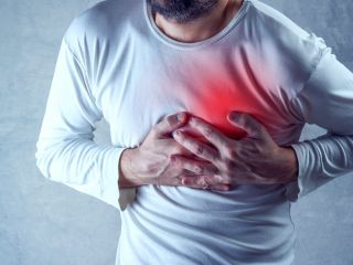 Man holding his hands over his chest as if experiencing heart attack