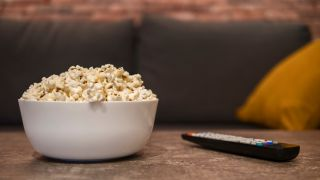 A bowl of popcorn on a coffee table.