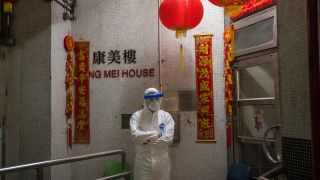 An official wearing protective gear stands guard outside an entrance to the Hong Mei House residential building at Cheung Hong Estate in Hong Kong on Feb. 11, 2020, following the evacuation of more than 100 people from the housing block after residents in two different apartments tested positive for the new coronavirus.