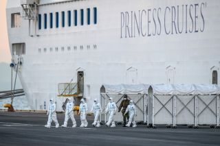 Emergency workers exit the Diamond Princess cruise ship where thousands remain quarantined.