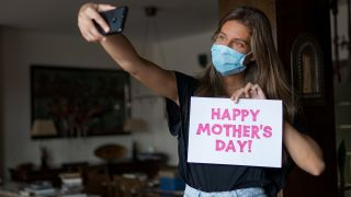 Girl wearing a mask is taking a selfie for mother's day during COVID-19.