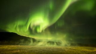 This shot shows Iceland's famous geyser, the Great Geysir, preparing to blow, with the aurora behind it.